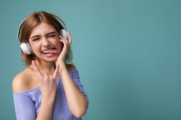 Foto de uma jovem loira atraente e emocional usando uma blusa cortada azul isolada em um fundo azul