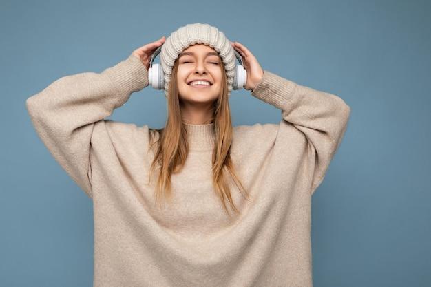 Foto de uma jovem loira bonita e sexy, feliz e sorridente, vestindo um suéter bege de inverno e um chapéu
