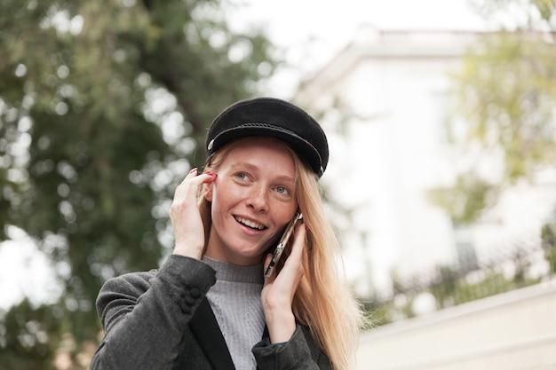 Foto de uma jovem loira de olhos azuis com manicure vermelha caminhando pelo parque da cidade no fim de semana e conversando ao telefone, colocando o cabelo atrás da orelha e sorrindo ligeiramente