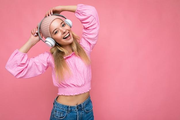 Foto de uma jovem loira sorridente e atraente usando uma blusa rosa e um chapéu rosa isolado