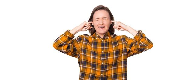 Foto de uma jovem louca, gritando com os olhos e ouvidos fechados