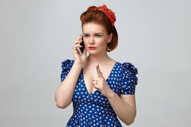 Foto de uma jovem mãe zangada em uma roupa vintage com aparência rigorosa, levantando o dedo indicador na frente dela como um sinal de alerta