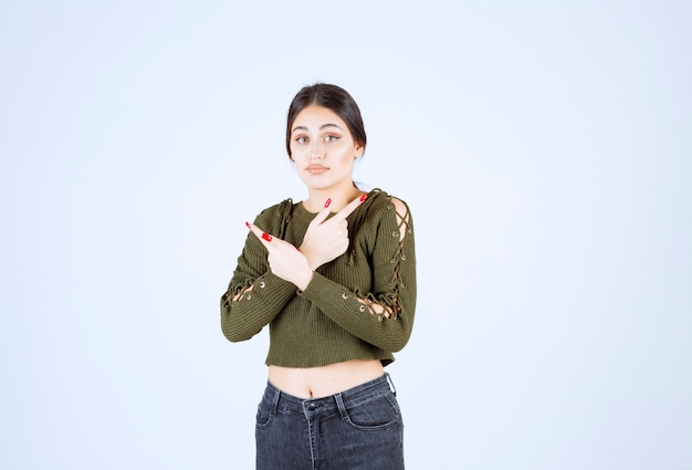 Foto de uma jovem modelo em pé e apontando para o lado com o dedo indicador.