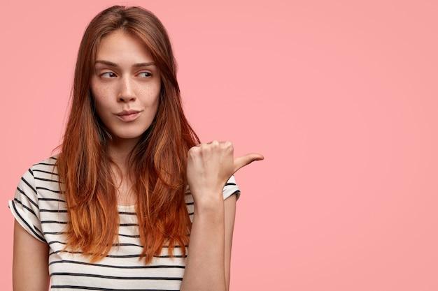 Foto de uma jovem modelo feminina com pele sardenta e saudável, parece misteriosamente de lado, indica com o polegar contra uma parede rosa com espaço de cópia