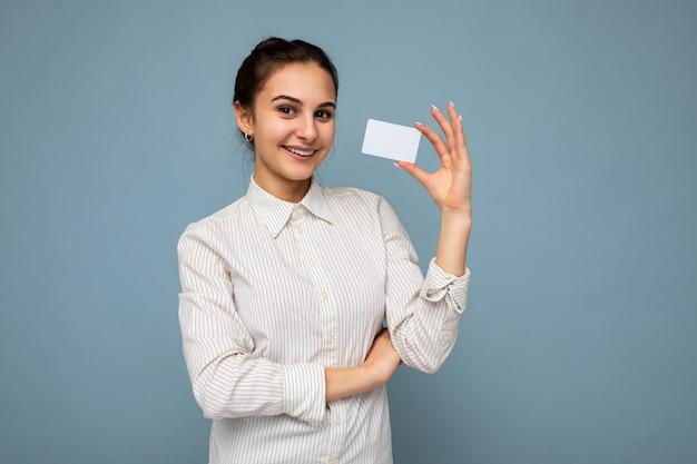 Foto de uma jovem morena atraente sorridente, positiva, usando blusa branca
