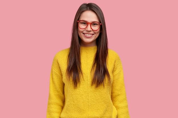 Foto de uma jovem morena bonita satisfeita com uma expressão feliz na cintura, usando óculos e um macacão amarelo casual, modelos contra um fundo rosa
