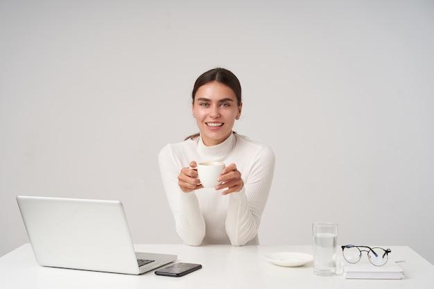 Foto de uma jovem morena charmosa em poloneck de malha branca, sentada à mesa com uma xícara de chá nas mãos levantadas, olhando alegremente com um largo sorriso, isolada sobre uma parede branca