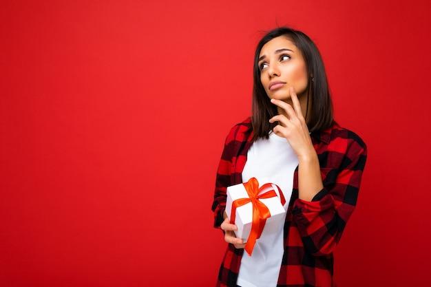 Foto de uma jovem morena pensativa muito positiva, isolada sobre uma parede de fundo vermelho