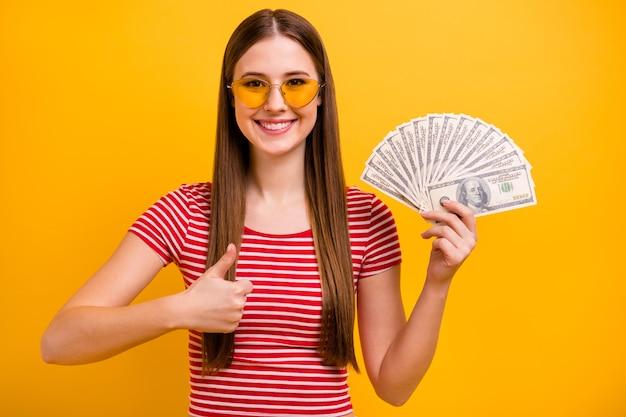 Foto de uma jovem muito fofa segurando dólares, torcedor de dinheiro, aprovando a obtenção de crédito, banco confiável, suporte empresarial, desgaste, óculos solares, camisa vermelha, branca, listrada, cor amarela vibrante, fundo