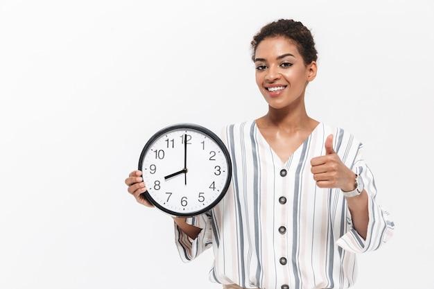 Foto de uma jovem mulher africana bonita posando isolada sobre a parede branca, segurando o relógio de ponto aparecendo os polegares.