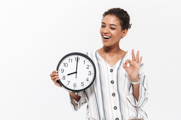 Foto de uma jovem mulher africana bonita posando isolada sobre a parede branca, segurando o relógio de ponto mostrando o gesto certo.