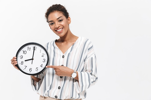 Foto de uma jovem mulher africana bonita posando isolada sobre uma parede branca, segurando o relógio de ponto apontando.