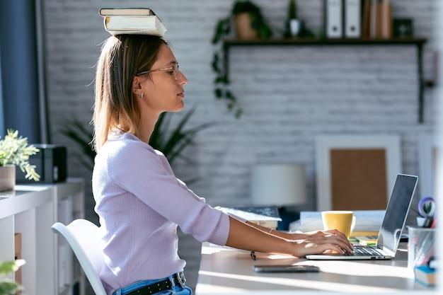 Foto de uma jovem mulher atraente na mesa com livros na cabeça enquanto trabalhava com o computador em casa.