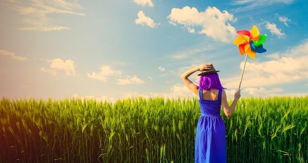 Foto de uma jovem mulher bonita com cata-vento no campo