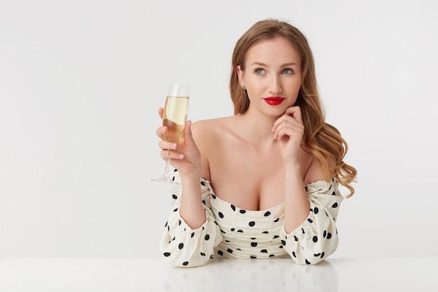 Foto de uma jovem mulher bonita com longos cabelos loiros e lábios vermelhos, inclinando-se no braço, pensa em seu amante, sorrisos tristemente isolados sobre uma parede branca.