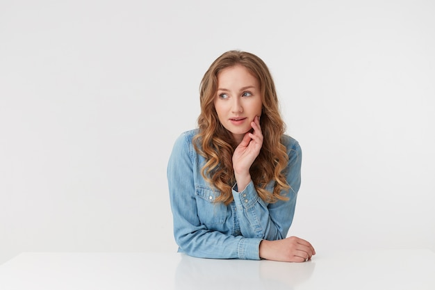 Foto de uma jovem mulher bonita com longos cabelos loiros ondulados, vestindo uma camisa jeans, situada à mesa apóia seu queixo com a mão, pensando em algo olhando para longe isolado sobre fundo branco.