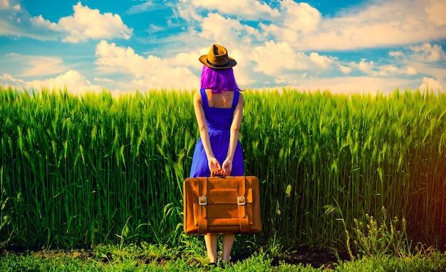 Foto de uma jovem mulher bonita com mala no campo. conceito de temporada de verão