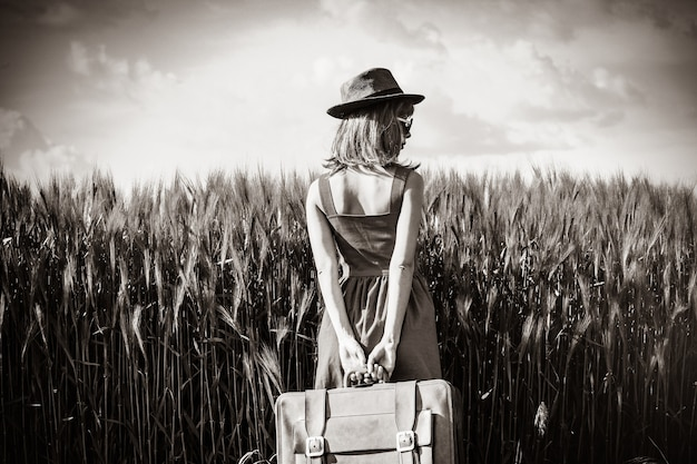 Foto de uma jovem mulher bonita com mala no campo. imagem em estilo de cor preto e branco