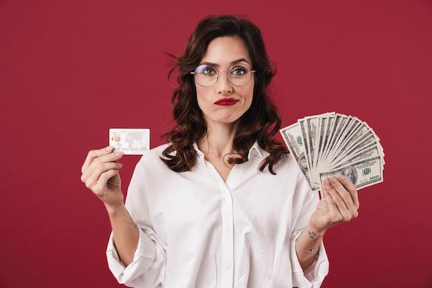 Foto de uma jovem mulher bonita confusa isolada na parede vermelha, segurando dinheiro e cartão de crédito.