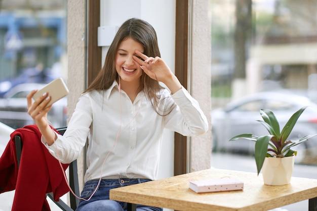 Foto de uma jovem mulher bonita rindo com alegria usando seu telefone inteligente e fones de ouvido durante o conceito de mobilidade de tecnologia de positividade de comunicação de videoconferência.