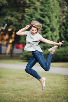Foto de uma jovem mulher branca com cabelo louro em uma camiseta azul, jeans e tênis salta e se alegra