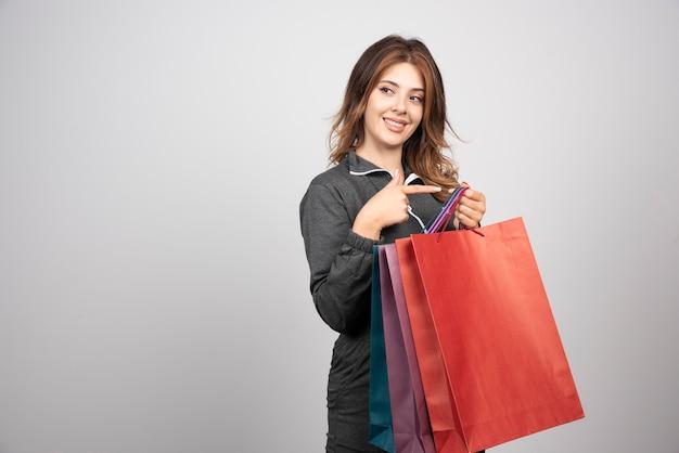 Foto de uma jovem mulher com sacolas de compras e acenando com a mão.