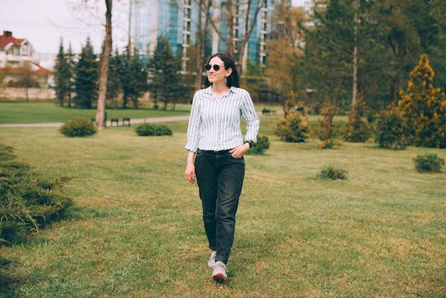 Foto de uma jovem mulher de negócios caminhando no parque durante o tempo livre
