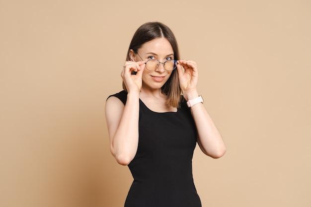 Foto de uma jovem mulher de negócios caucasiana feliz usando óculos em pé sobre uma parede bege