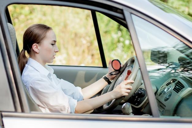 Foto de uma jovem mulher de negócios fazendo maquiagem enquanto dirige um carro no engarrafamento