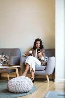 Foto de uma jovem mulher de negócios feliz enviando mensagens de texto com seu smartphone na cafeteria.