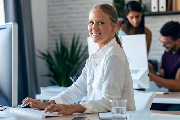 Foto de uma jovem mulher de negócios loira linda trabalhando com computador enquanto sorrindo, olhando para a câmera. no fundo, seus colegas trabalhando juntos no escritório.