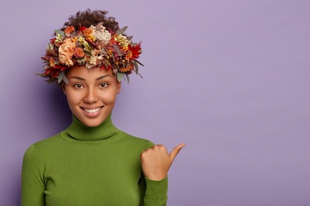 Foto de uma jovem mulher encaracolada de pele escura aponta o polegar para longe, usa uma gola verde, grinalda outonal, tem um sorriso agradável, demonstra espaço de cópia para seu conteúdo de publicidade, dá sugestões