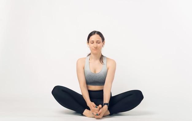 Foto de uma jovem mulher esportiva sentada em pose de alongamento de borboleta no estúdio