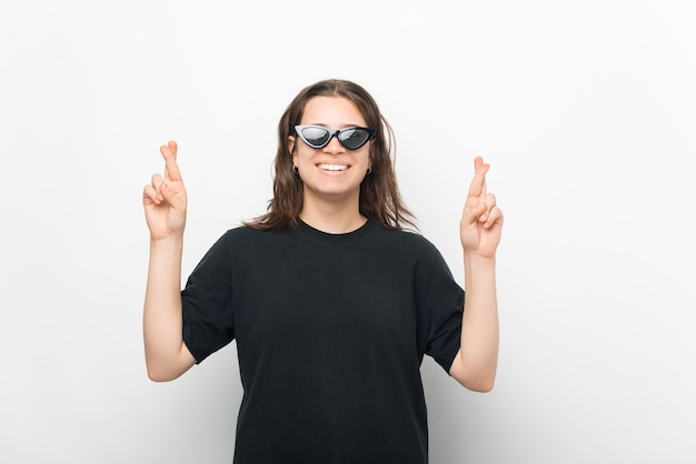 Foto de uma jovem mulher na moda usando óculos escuros, cruzando os dedos e fazendo um pedido