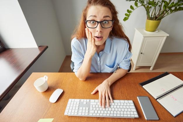 Foto de uma jovem mulher surpresa segurando o rosto em choque