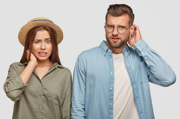 Foto de uma jovem namorada confusa e namorado coçando a cabeça de espanto, com expressões faciais confusas e indecisas