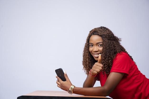 Foto de uma jovem negra animada usando o telefone e fazendo sinal de positivo