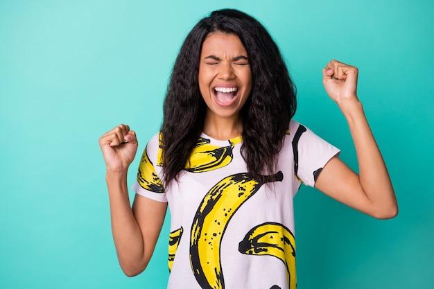 Foto de uma jovem negra louca levantando as mãos, boca aberta, olhos fechados e vestindo uma camiseta com estampa de banana isolada no fundo da cor turquesa