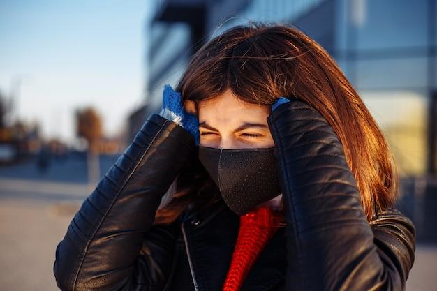 Foto de uma jovem perto de um shopping fechado lutando com uma dor de cabeça e segurando a cabeça dela com as mãos