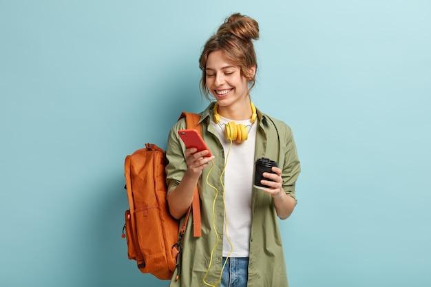 Foto de uma jovem positiva em roupas casuais, baixa arquivo multimídia no celular, tem fones de ouvido no pescoço