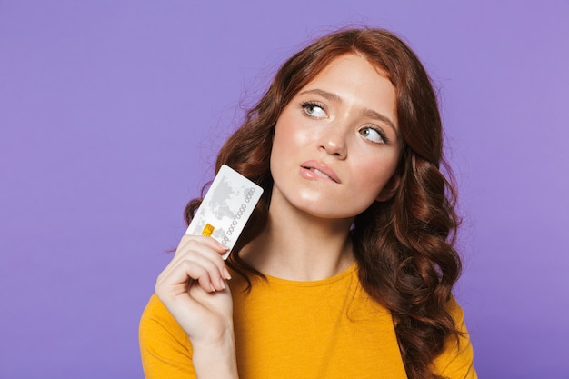Foto de uma jovem ruiva vestindo roupas amarelas segurando um cartão de crédito de plástico e olhando para cima sobre o roxo
