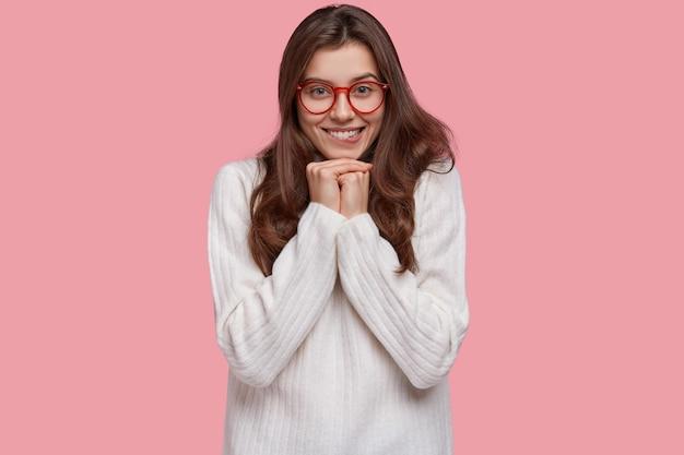 Foto de uma jovem satisfeita com a cintura para cima morde os lábios, tem uma expressão feliz, mantém as mãos embaixo do queixo e usa roupas grandes