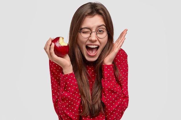 Foto de uma jovem satisfeita pisca os olhos, levanta a mão perto da cabeça, morde maçã fresca e tem uma expressão alegre, vestida com uma blusa de bolinhas vermelhas