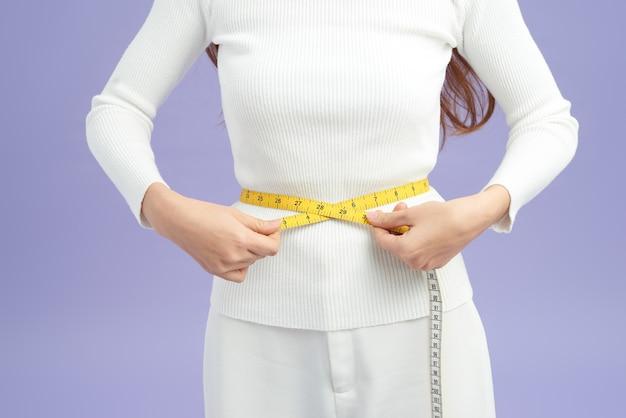 Foto de uma jovem saudável e em forma medindo a cintura com uma fita métrica em centímetros e milímetros.