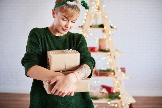 Foto de uma jovem segurando uma pilha de presentes