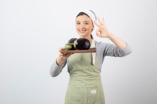 Foto de uma jovem segurando uma placa de madeira com berinjelas e fazendo um gesto de ok