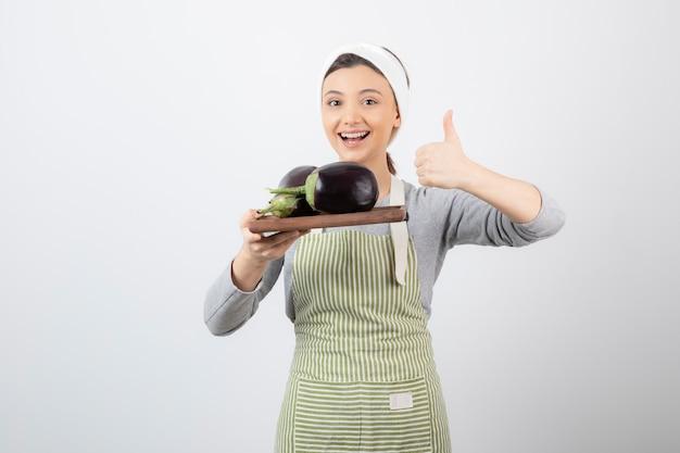 Foto de uma jovem segurando uma placa de madeira com berinjelas e mostrando o polegar