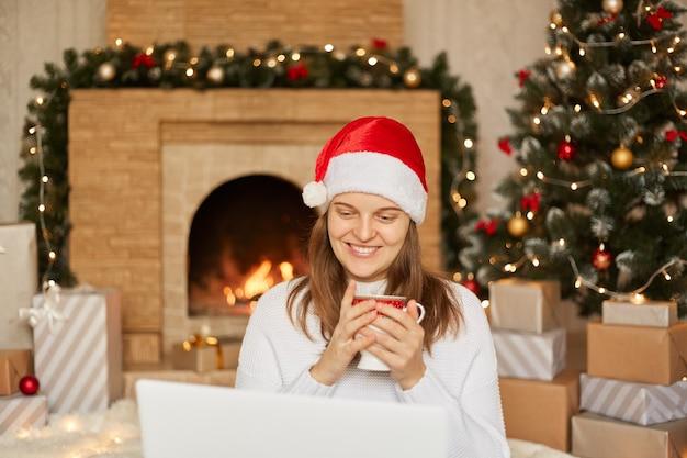 Foto de uma jovem sentada em frente ao laptop, segurando uma xícara com chá quente, olhando para a tela, usando um chapéu de papai noel vermelho e um suéter branco na sala de estar de natal decorada, parabeniza alguém com o feriado