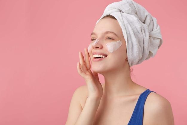 Foto de uma jovem simpática alegre com beleza natural com uma toalha na cabeça depois do banho, levanta-se e coloca creme para o rosto, desvia o olhar.