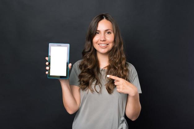 Foto de uma jovem sorridente apontando para uma tela em branco no tablet